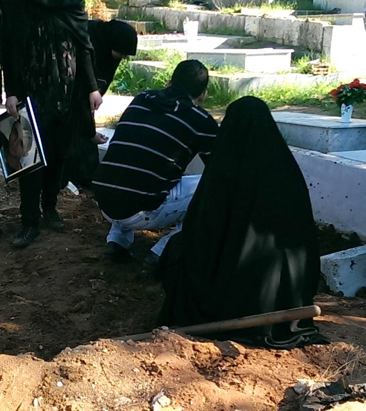 the young man who lost his life in the Beirut bombing, was lowered into his final resting place. The woman standing over the dirt that covers him and holding his picture was his wife to be - they were supposed to marry this coming summer.
